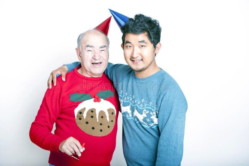 Πορτρέτο ενός ανώτερου ενήλικου ατόμου και ενός νέου ασιατικού ατόμου που φορούν τους άλτες Χριστουγέννων και τα καπέλα κομμάτων στοκ εικόνες