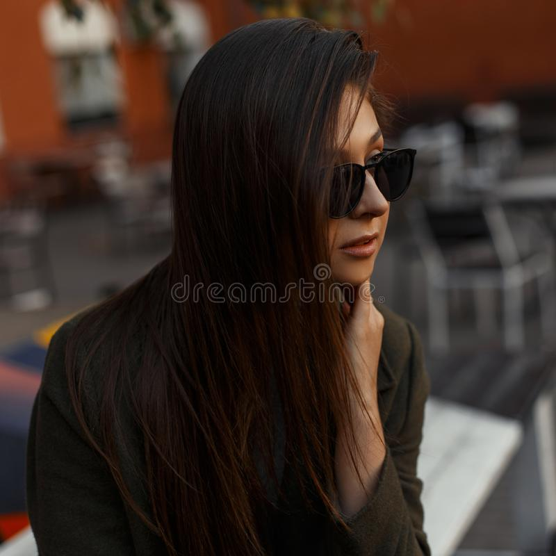 Πορτρέτο ενός αρκετά ελκυστικού και νέου κοριτσιού brunette στα λαμπρά μαύρα μοντέρνα γυαλιά και τα καθιερώνοντα τη μόδα ενδύματα στοκ φωτογραφία με δικαίωμα ελεύθερης χρήσης