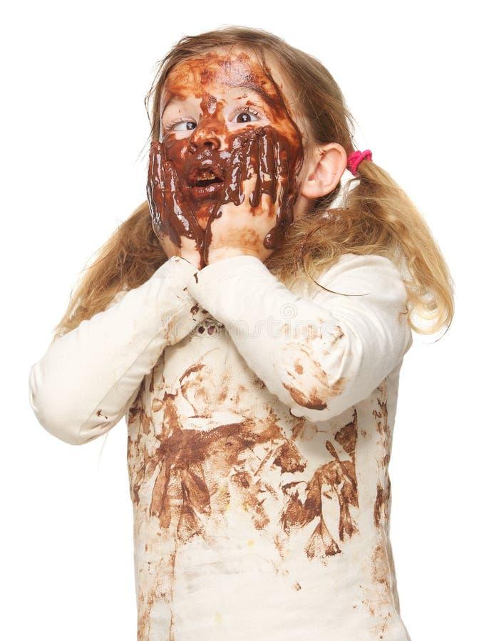 Πορτρέτο ενός αστείου μικρού κοριτσιού το βρώμικο πρόσωπο που καλύπτεται με στη σοκολάτα στοκ εικόνες