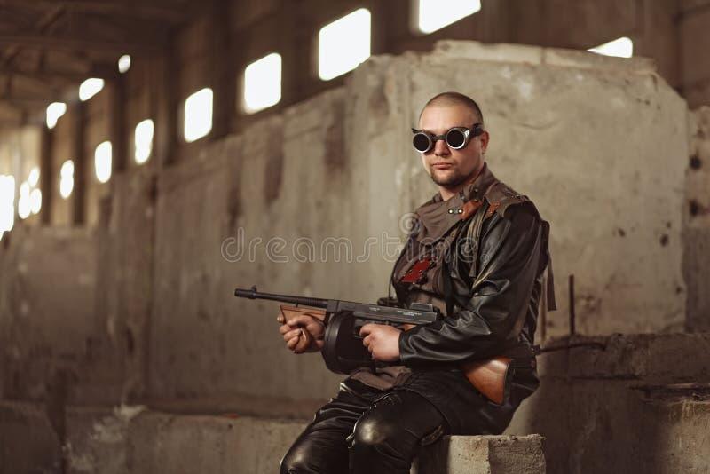 Πορτρέτο ενός ατόμου από τον μετα-αποκαλυπτικό κόσμο με το πολυβόλο και των μαύρων γυαλιών σε ένα εγκαταλειμμένο κτήριο στοκ φωτογραφία