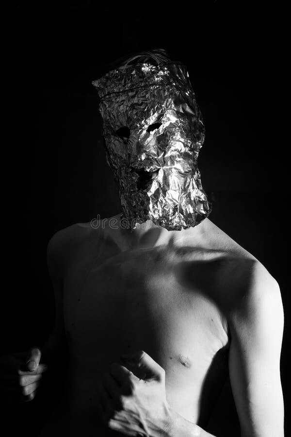 Πορτρέτο ενός ατόμου που ντύνεται στο τρομακτικό φύλλο αλουμινίου μασκών στοκ φωτογραφία