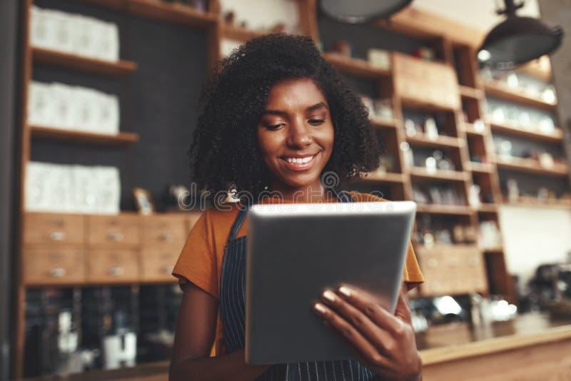 Πορτρέτο ενός αφρικανικού θηλυκού ιδιοκτήτη καφέδων που χρησιμοποιεί την ψηφιακή ταμπλέτα στοκ εικόνες