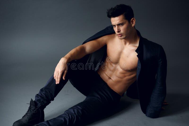 Πορτρέτο ενός βέβαιου, προκλητικού νεαρού άνδρα, με το γυμνό κορμό με το σακάκι στους ώμους του, που απομονώνονται στο γκρίζο υπό στοκ εικόνες με δικαίωμα ελεύθερης χρήσης