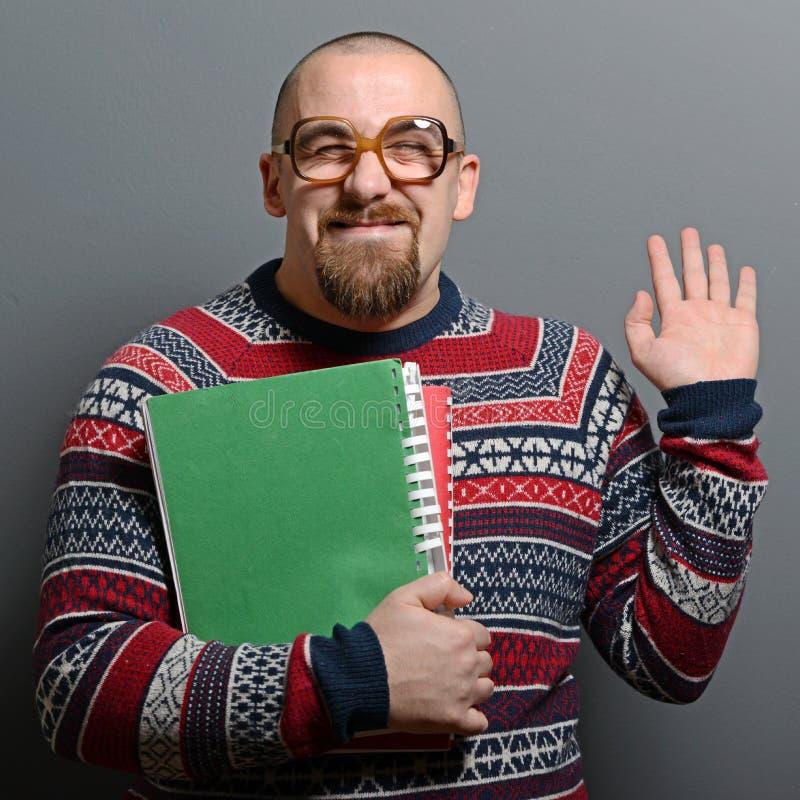 Πορτρέτο ενός βιβλίου εκμετάλλευσης nerd με τα αναδρομικά γυαλιά στο γκρίζο κλίμα στοκ φωτογραφίες με δικαίωμα ελεύθερης χρήσης