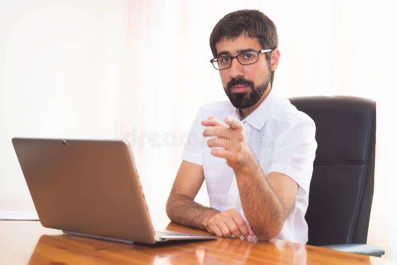 Πορτρέτο ενός γενειοφόρου ατόμου στο γραφείο που δείχνει σε σας στοκ εικόνες