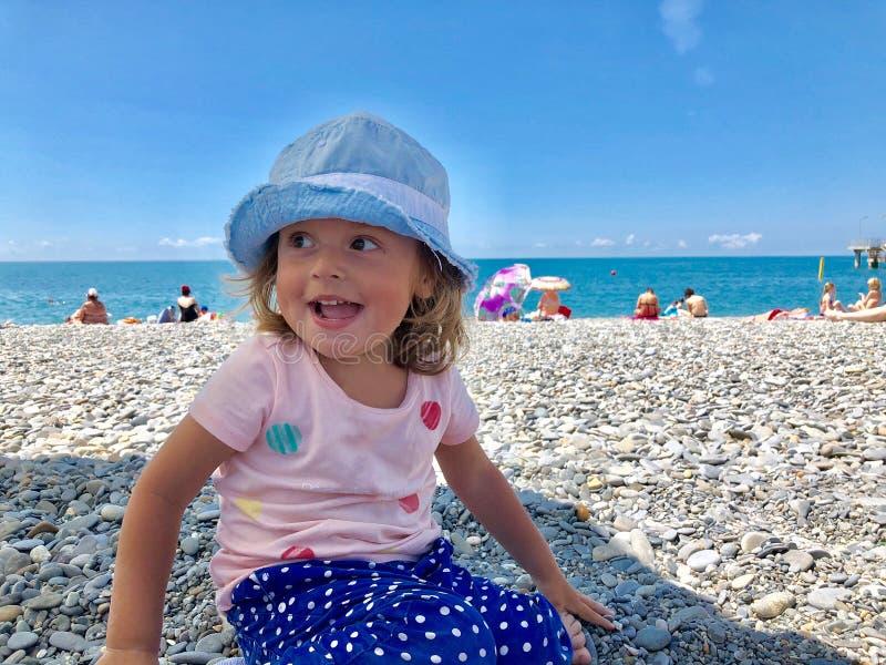 Πορτρέτο ενός γοητευτικού μικρού κοριτσιού σε μια παραλία χαλικιών στοκ φωτογραφίες