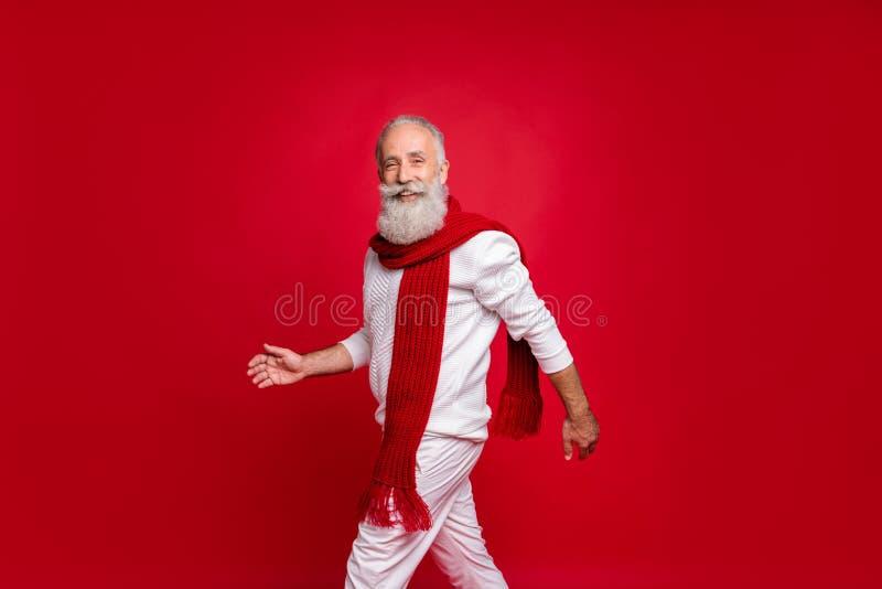 Πορτρέτο ενός ελκυστικού συνταξιούχου που χαμογελά φορώντας λευκά παντελόνια για τζάμπινγκ σε κόκκινο φόντο στοκ εικόνες
