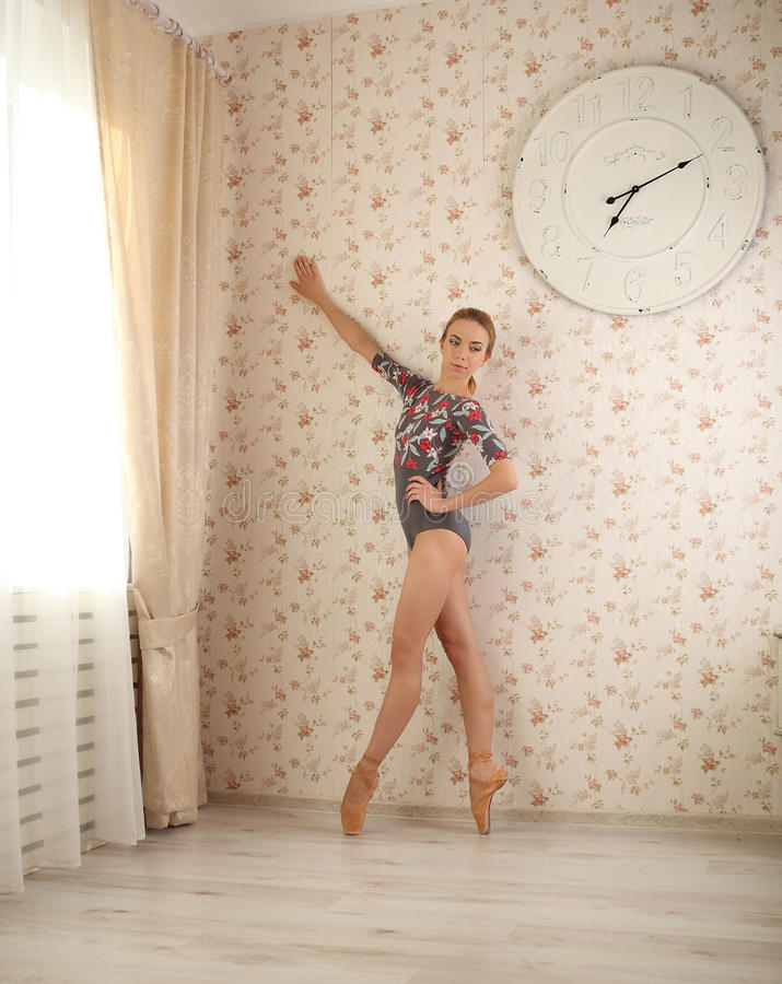 Πορτρέτο ενός επαγγελματικού ballerina tiptoe κοντά στο παράθυρο στο φως ήλιων στο εγχώριο εσωτερικό Έννοια μπαλέτου στοκ φωτογραφία