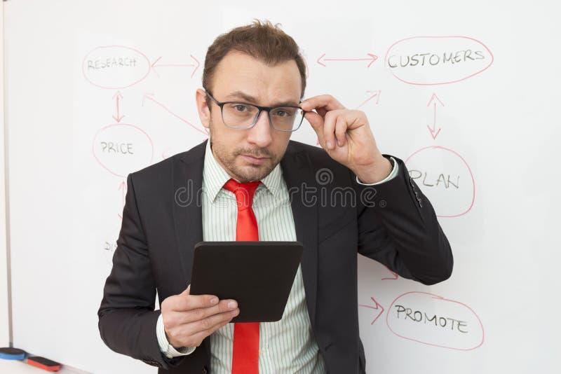 Πορτρέτο ενός επιχειρηματία με μια ψηφιακή ταμπλέτα Διάγραμμα ροής στο υπόβαθρο στοκ εικόνα