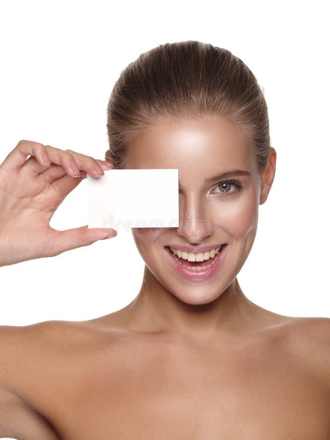 Πορτρέτο ενός ευρωπαϊκού νέου χαμογελώντας κοριτσιού με το υγιές τέλειο ομαλό δέρμα, το οποίο κρατά μια κάρτα επιχειρησιακής επίσ στοκ εικόνα με δικαίωμα ελεύθερης χρήσης