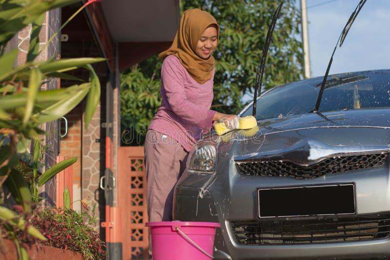 Πορτρέτο ενός ευτυχούς ασιατικού αυτοκινήτου πλύσης γυναικών hijab μπροστά από το γκαράζ της στοκ εικόνες