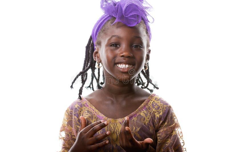Πορτρέτο ενός ευτυχούς αφρικανικού μικρού κοριτσιού στο πορφυρό κοστούμι απομονωμένος στοκ φωτογραφίες