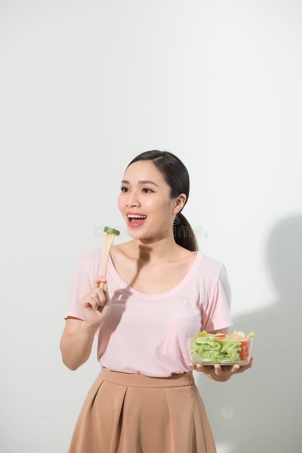 Πορτρέτο ενός ευτυχούς εύθυμου κοριτσιού που τρώει τη φρέσκια σαλάτα από ένα κύπελλο και ένα κλείσιμο του ματιού που απομονώνοντα στοκ φωτογραφίες