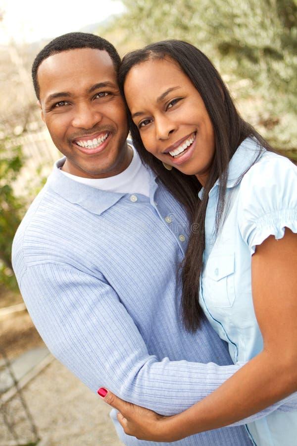 Πορτρέτο ενός ευτυχούς ζεύγους αφροαμερικάνων που χαμογελά και που αγκαλιάζει στοκ φωτογραφία