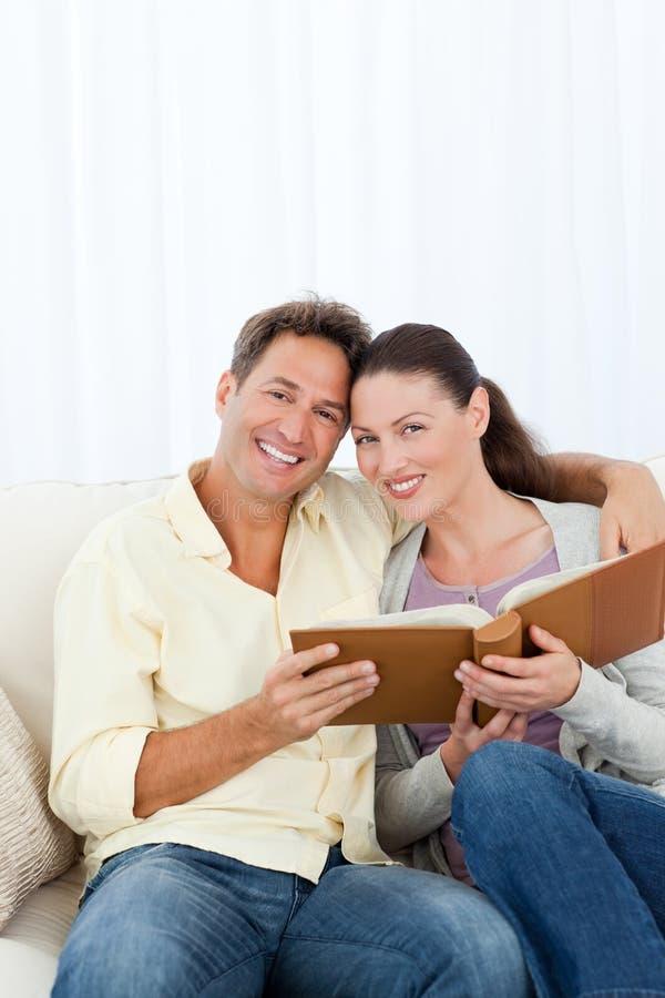 Πορτρέτο ενός ευτυχούς ζεύγους που φαίνεται ένα λεύκωμα φωτογραφιών στοκ εικόνες