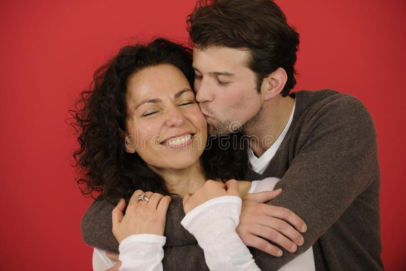 Πορτρέτο ενός ευτυχούς ζεύγους στο κόκκινο υπόβαθρο στοκ φωτογραφία με δικαίωμα ελεύθερης χρήσης
