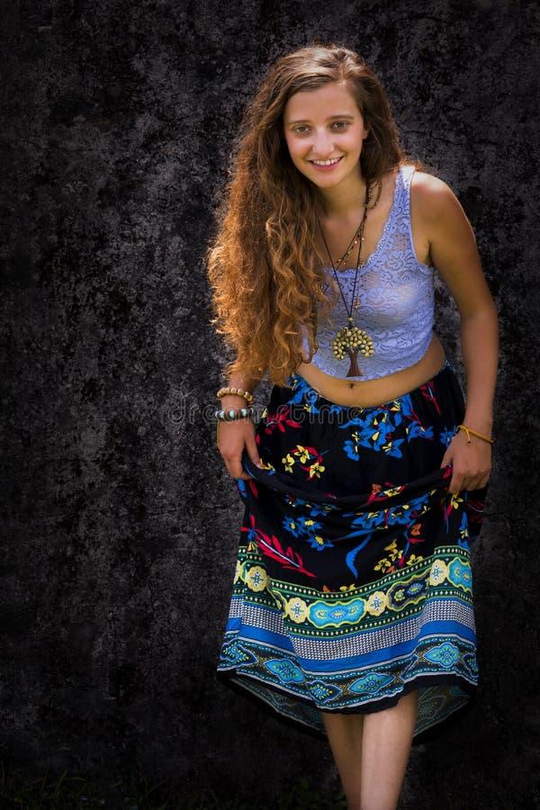 Πορτρέτο ενός ευτυχούς νέου κοριτσιού και μιας ντυμένης floral μεγάλου μεγέθους φούστας με την κορυφή στοκ εικόνα
