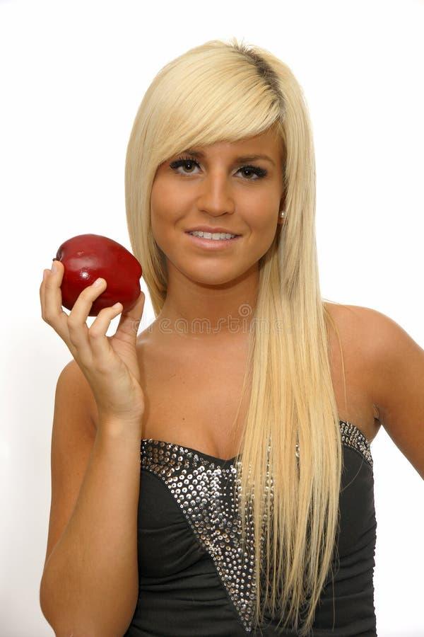 Πορτρέτο ενός ευτυχούς νέου κοριτσιού που κρατά το κόκκινο μήλο στοκ εικόνα