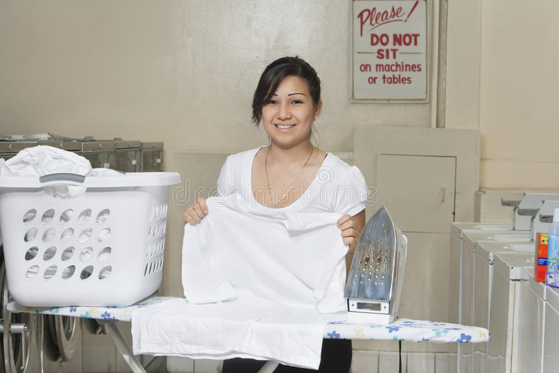 Πορτρέτο ενός ευτυχούς νέου σιδερώματος υπαλλήλων Laundromat στοκ εικόνες