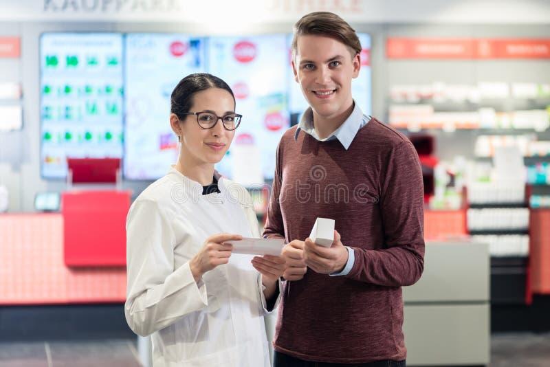 Πορτρέτο ενός ευτυχούς πελάτη δίπλα σε έναν χρήσιμο φαρμακοποιό στοκ εικόνες