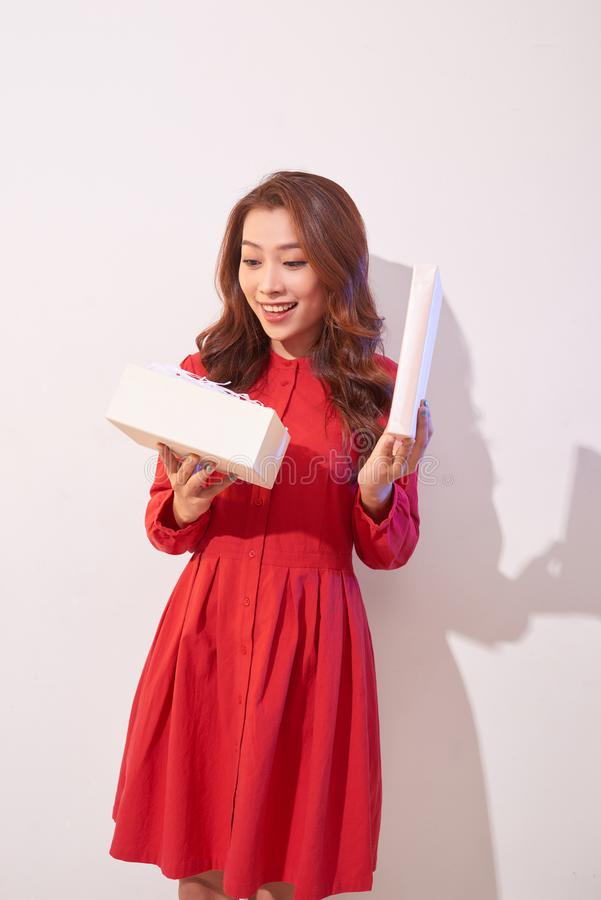 Πορτρέτο ενός ευτυχούς χαμογελώντας κοριτσιού που ανοίγει ένα κιβώτιο δώρων που απομονώνεται πέρα από το άσπρο υπόβαθρο στοκ φωτογραφία με δικαίωμα ελεύθερης χρήσης