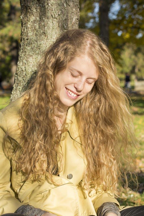 Πορτρέτο ενός ευτυχούς χαμόγελου ξανθού σε ένα πάρκο στοκ εικόνες