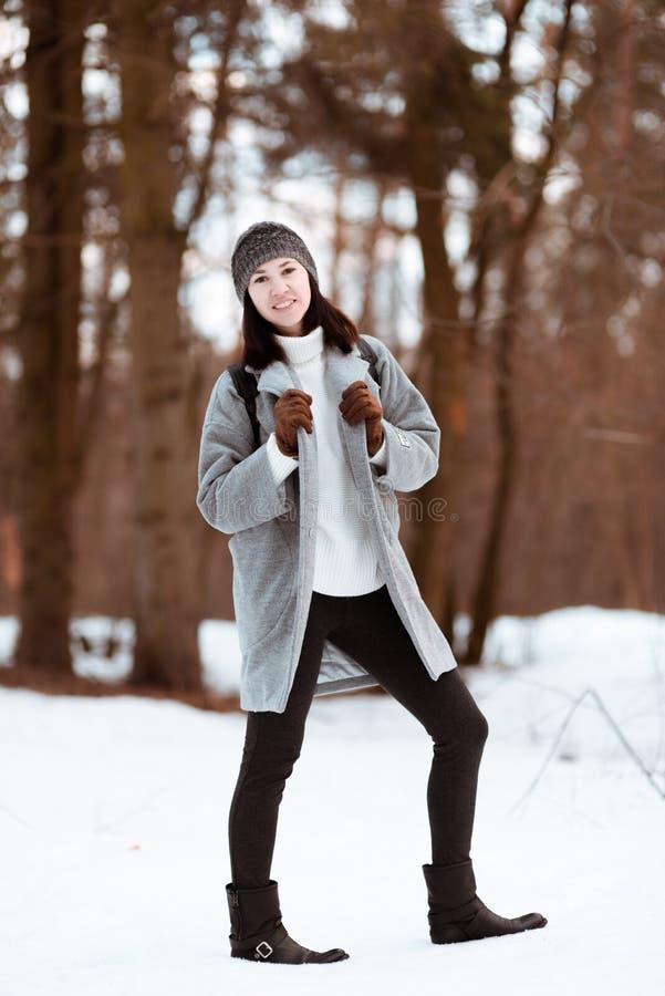 Πορτρέτο ενός ευτυχούς όμορφου κοριτσιού με την καφετιά τρίχα στο χειμερινό δάσος που ντύνεται σε ένα ύφος hipster, τρόπος ζωής στοκ εικόνες