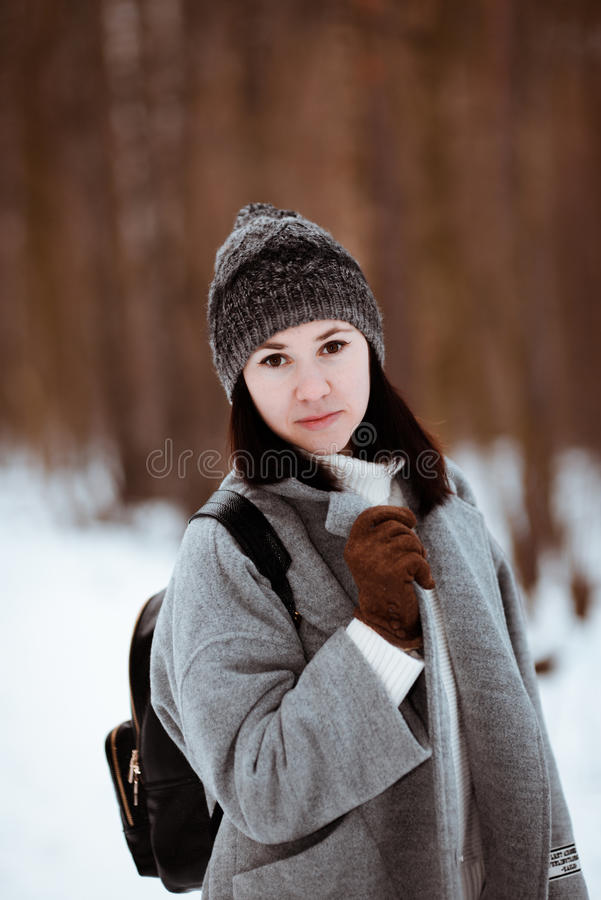 Πορτρέτο ενός ευτυχούς όμορφου κοριτσιού με την καφετιά τρίχα στο χειμερινό δάσος που ντύνεται σε ένα ύφος hipster, τρόπος ζωής στοκ φωτογραφία με δικαίωμα ελεύθερης χρήσης