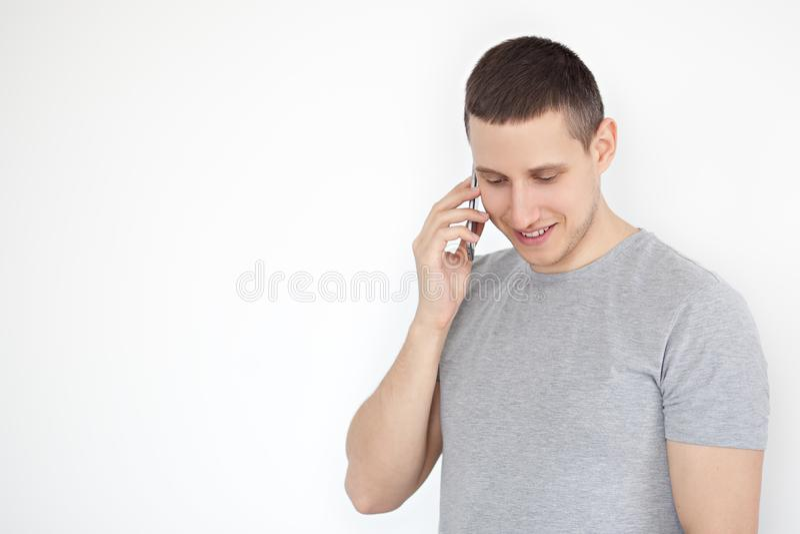 Πορτρέτο ενός εύθυμου, θετικού, ελκυστικού τύπου με τις καλαμιές σε μια γκρίζα μπλούζα, που μιλά στο τηλέφωνο σε ένα γκρίζο υπόβα στοκ φωτογραφία με δικαίωμα ελεύθερης χρήσης
