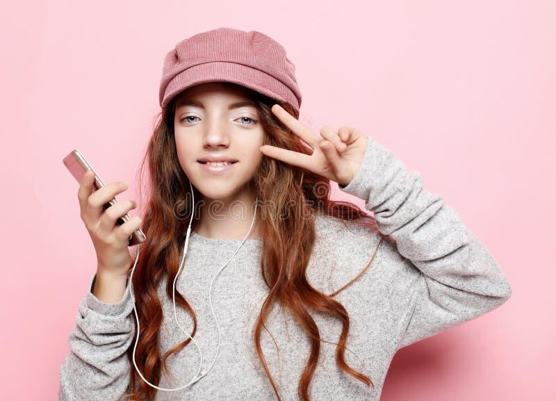 Πορτρέτο ενός εύθυμου μικρού κοριτσιού με τη σγουρή τρίχα λ που παίρνει ένα selfie που απομονώνεται πέρα από το ρόδινο υπόβαθρο στοκ φωτογραφία