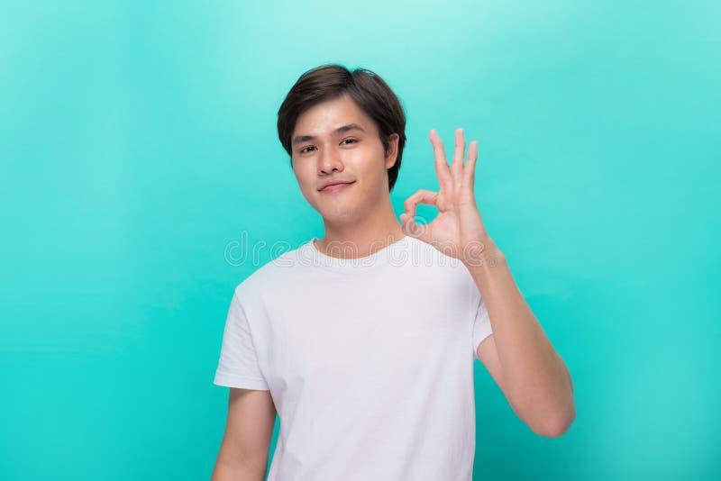 Πορτρέτο ενός εύθυμου νεαρού άνδρα που παρουσιάζει εντάξει απομονωμένο χειρονομία ο στοκ εικόνες