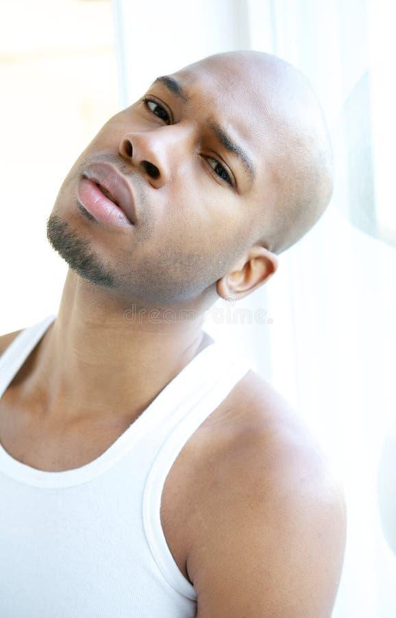 Πορτρέτο ενός ελκυστικού νεαρού άνδρα που χαλαρώνει από το παράθυρο στοκ φωτογραφίες