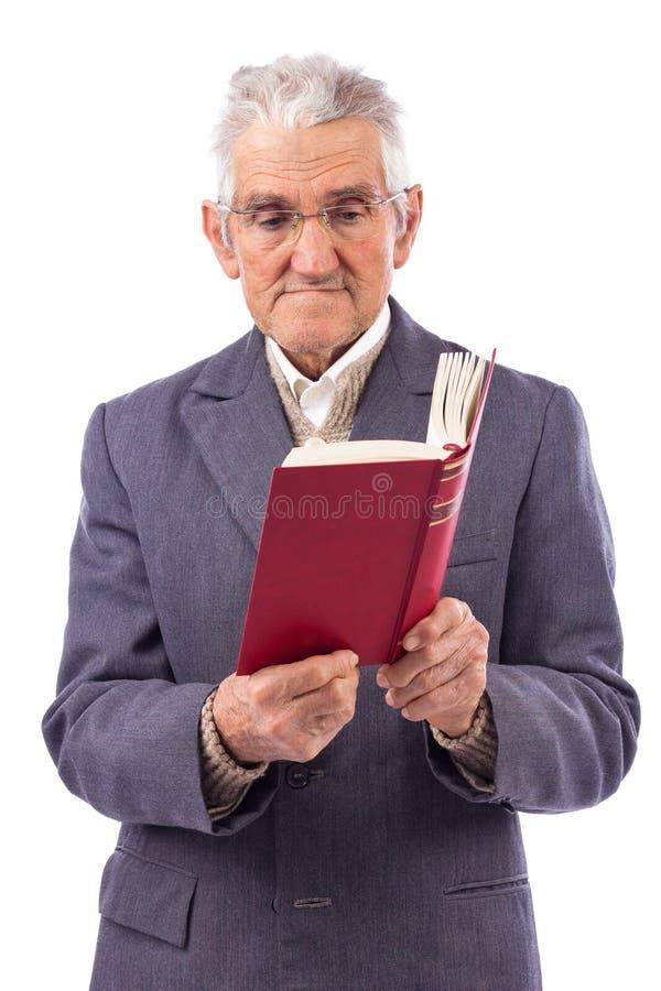 Πορτρέτο ενός ηληκιωμένου με τα γυαλιά που διαβάζει ένα βιβλίο στοκ φωτογραφία