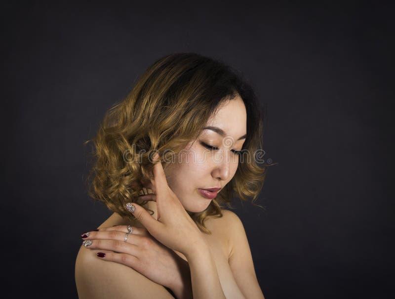 Πορτρέτο ενός κοριτσιού με τους γυμνούς ώμους, με την τρίχα και makeup σε ένα σκοτεινό υπόβαθρο στοκ εικόνες με δικαίωμα ελεύθερης χρήσης