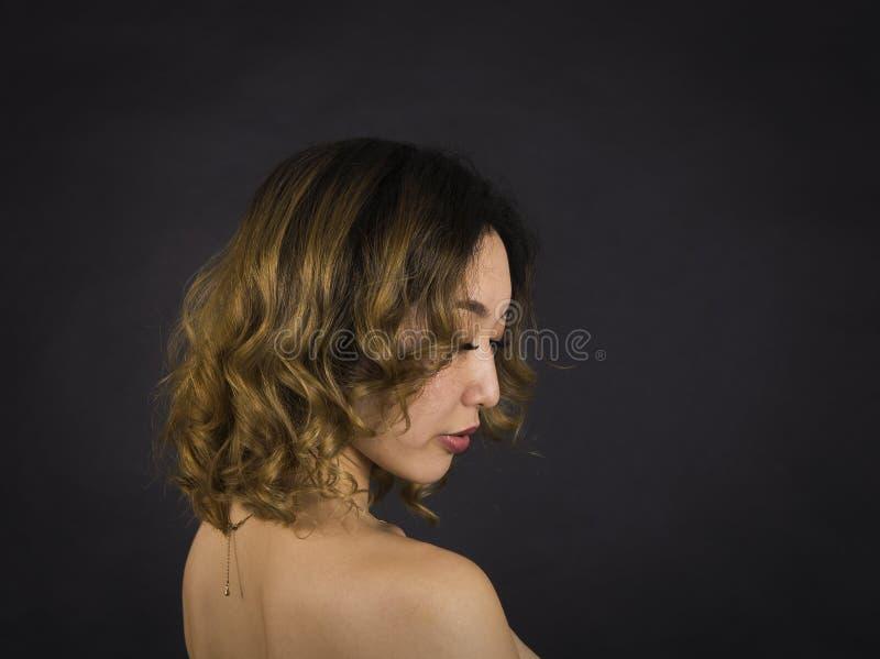 Πορτρέτο ενός κοριτσιού με τους γυμνούς ώμους, με την τρίχα και makeup σε ένα σκοτεινό υπόβαθρο στοκ φωτογραφία