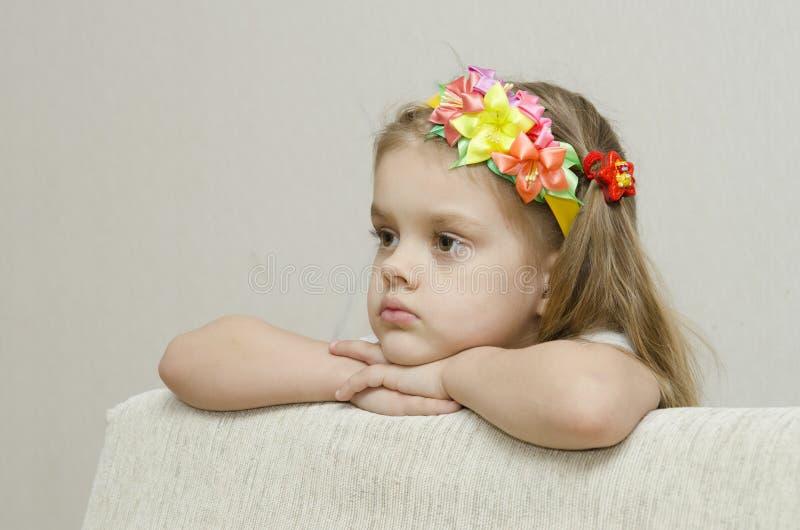 Πορτρέτο ενός κοριτσιού που φαίνεται σκεπτικά αριστερά κλίνοντας τον αγκώνα του στο πίσω μέρος του καναπέ στοκ φωτογραφία