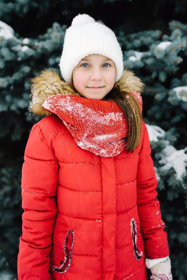 Πορτρέτο ενός κοριτσιού σε ένα κόκκινο σακάκι, κοντά στο πράσινο δέντρο στην οδό στοκ εικόνα με δικαίωμα ελεύθερης χρήσης