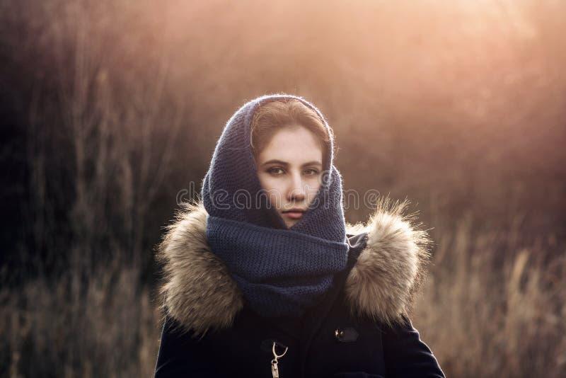 Πορτρέτο ενός κοριτσιού σε ένα πλεκτά σάλι και ένα φόρεμα, αναμμένο από το θερμό ήλιο στοκ φωτογραφίες