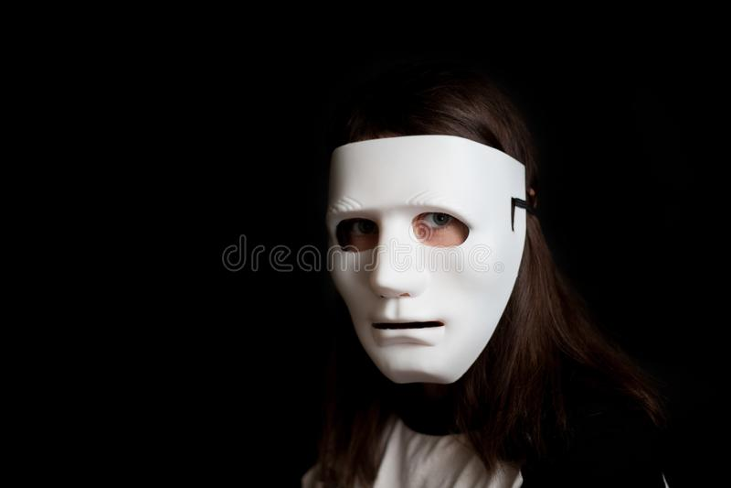 Πορτρέτο ενός κοριτσιού σε μια άσπρη μάσκα σε ένα μαύρο υπόβαθρο στοκ εικόνες με δικαίωμα ελεύθερης χρήσης