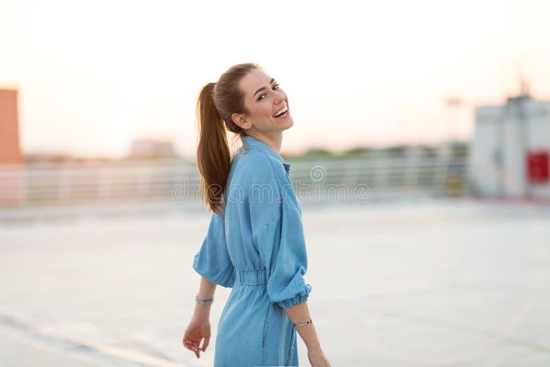 Πορτρέτο ενός κοριτσιού σε μια στέγη που απολαμβάνει το ηλιοβασίλεμα στοκ φωτογραφίες