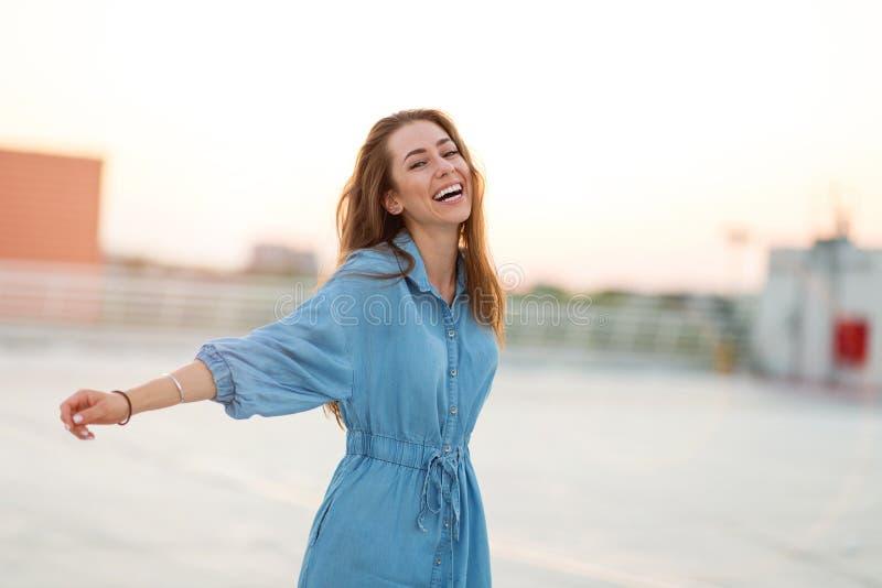 Πορτρέτο ενός κοριτσιού σε μια στέγη που απολαμβάνει το ηλιοβασίλεμα στοκ εικόνα