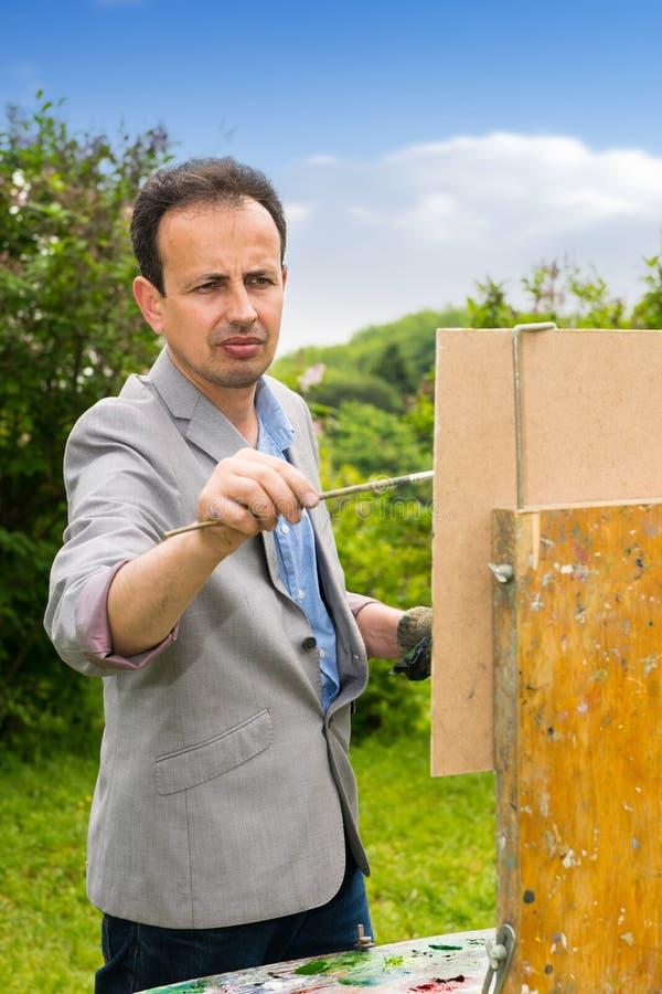 Πορτρέτο ενός μέσης ηλικίας αρσενικού καλλιτέχνη στη διαδικασία στοκ φωτογραφία