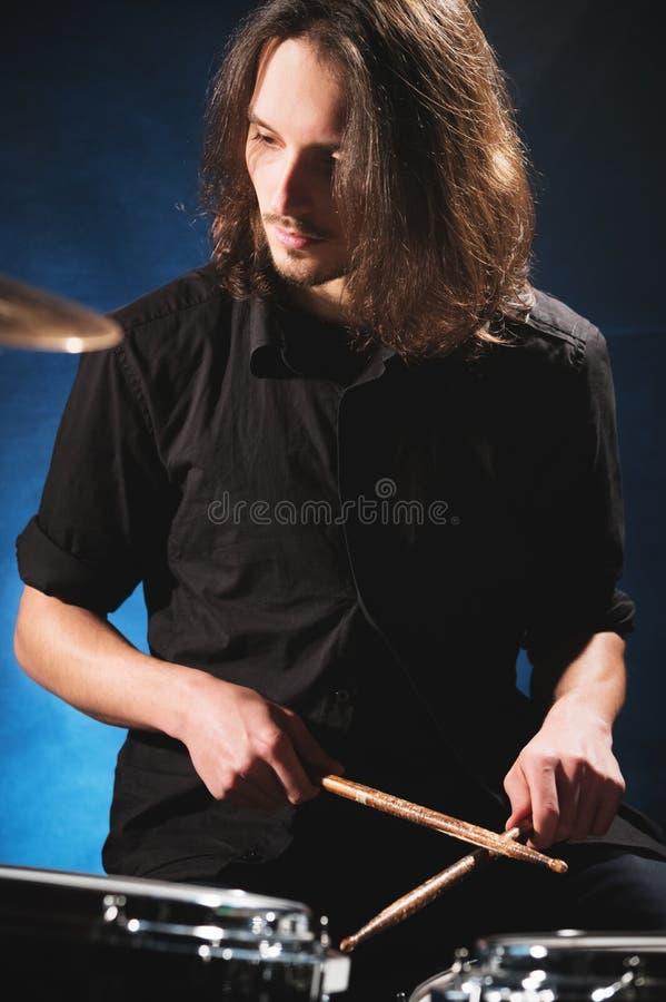 Πορτρέτο ενός μακρυμάλλους τυμπανιστή με chopsticks στα χέρια του που κάθεται πίσω από ένα σύνολο τυμπάνων Συγκρατημένος Έννοιες στοκ φωτογραφία με δικαίωμα ελεύθερης χρήσης