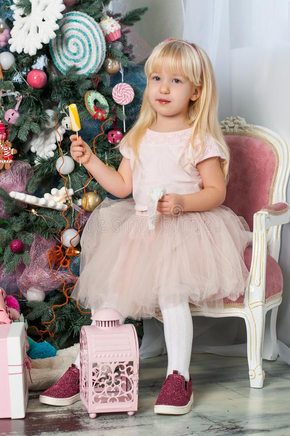 Πορτρέτο ενός μικρού καυκάσιου χαριτωμένου ξανθού κοριτσιού με χρωματισμένος lollipops στο εορταστικό νέο δωμάτιο στούντιο έτους στοκ εικόνα