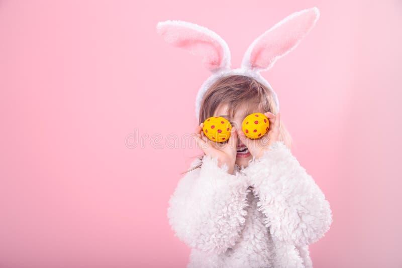 Πορτρέτο ενός μικρού κοριτσιού με τα αυτιά λαγουδάκι και τα αυγά Πάσχας στοκ εικόνες
