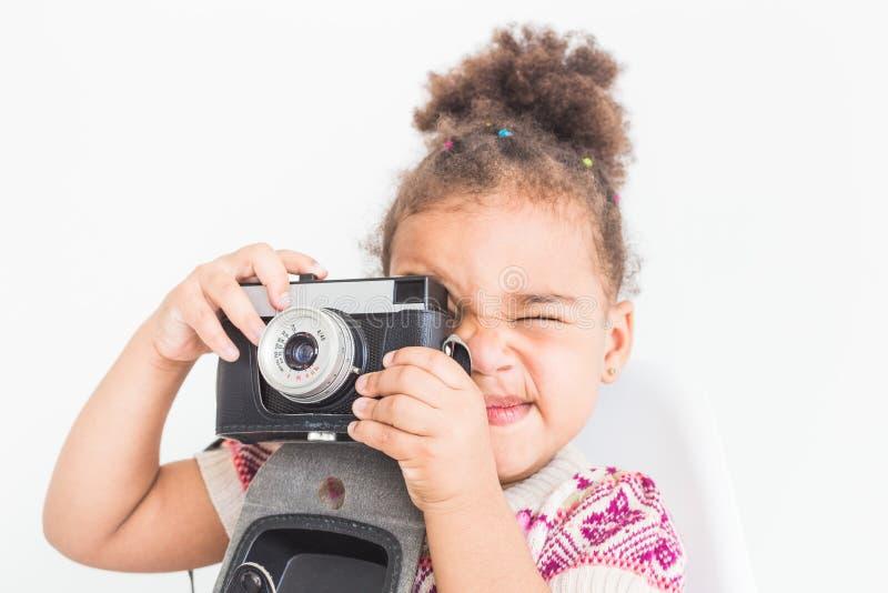 Πορτρέτο ενός μικρού κοριτσιού σε ένα ζωηρόχρωμο φόρεμα που παίρνει τις εικόνες σε μια παλαιά εκλεκτής ποιότητας κάμερα στοκ φωτογραφία με δικαίωμα ελεύθερης χρήσης