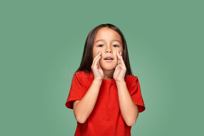Πορτρέτο ενός μικρού όμορφου κοριτσιού που στέκεται κατ' ευθείαν και που καλεί κάποιο που κρατά το χέρι της κοντά στο στόμα της στοκ φωτογραφία με δικαίωμα ελεύθερης χρήσης