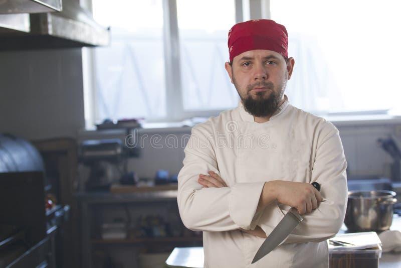 Πορτρέτο ενός μοντέρνου αρχιμάγειρα στο bandana που κρατά ένα μαχαίρι σε μια κουζίνα στοκ εικόνα