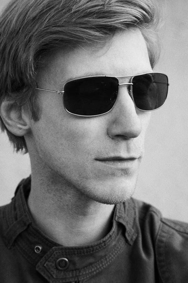 Πορτρέτο ενός μοντέρνου όμορφου νεαρού άνδρα στο σακάκι και τα γυαλιά ηλίου στοκ εικόνα με δικαίωμα ελεύθερης χρήσης