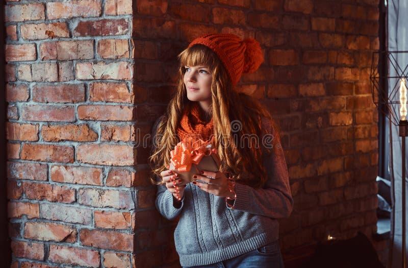 Πορτρέτο ενός μόνου redhead κοριτσιού που φορά ένα θερμά πουλόβερ και ένα καπέλο που κρατούν ένα κιβώτιο δώρων κλίνοντας σε έναν  στοκ εικόνες